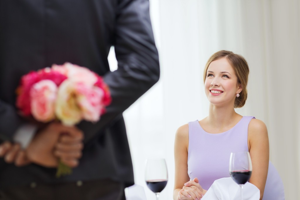 young woman looking at man with flower bouquet